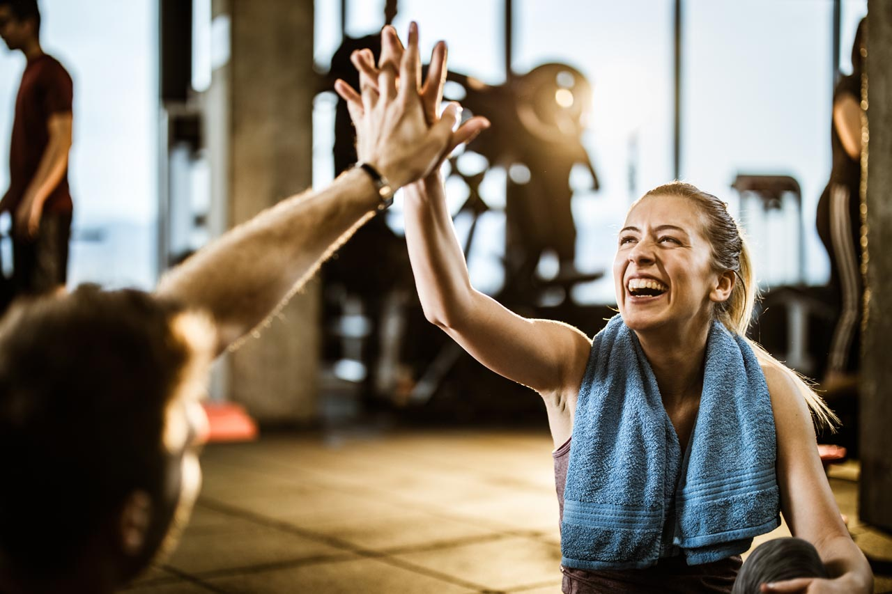 Happy female athlete having fun while giving her trainer high-five on a break in a gym.