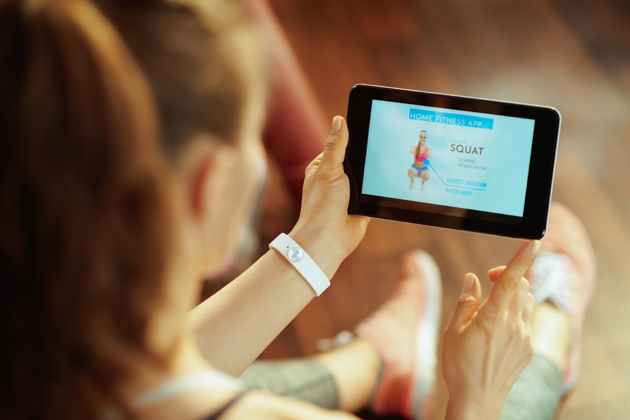 young sports woman using home workout trainer app in tablet PC